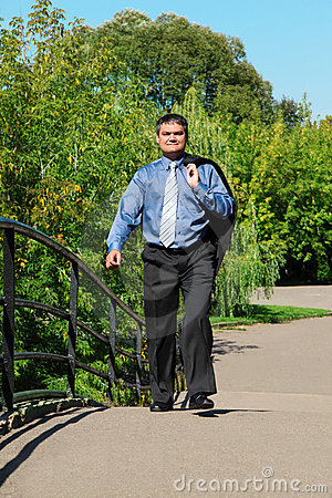 Businessman walks outdoor in summer
