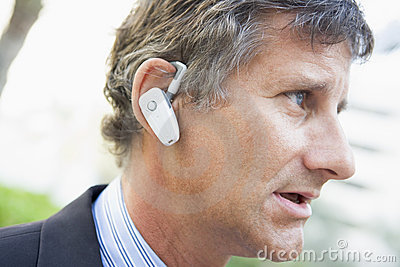 Businessman wearing earpiece outdoors