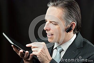Businessman Wearing Headset Using Tablet