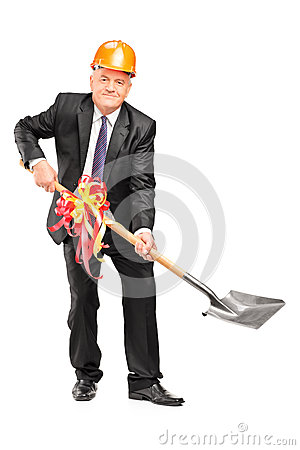 Businessman wearing helmet and holding a shovel with ribbon
