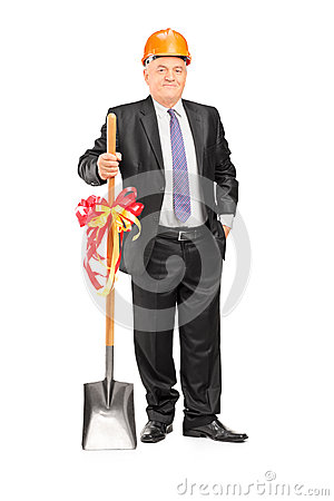 Businessman wearing helmet and holding a shovel with ribbon on i