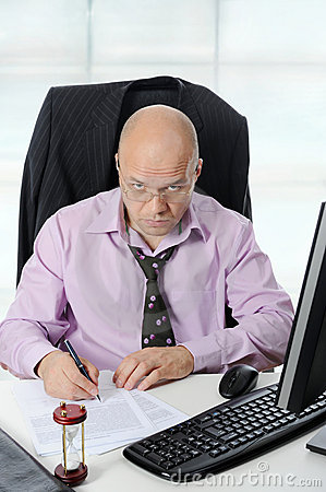 Businessman wearing spectacles sign documents.