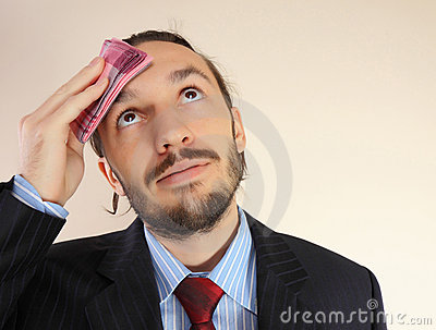 The businessman wipes a forehead by