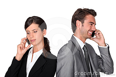 Businessman and woman with cellphones