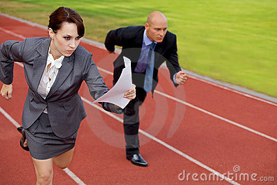 Businessman and woman running on race track