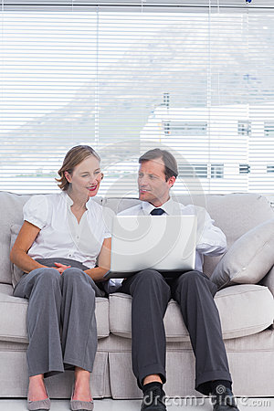 Businessman and woman sitting on couch and using laptop