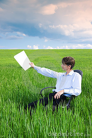 Businessman working on grassland under blue sky