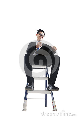 Businessman working on ladder