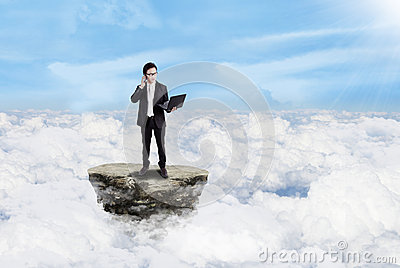 Businessman working with laptop above clouds