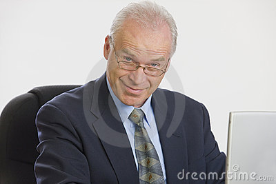 Businessman working on laptop looking at camera.