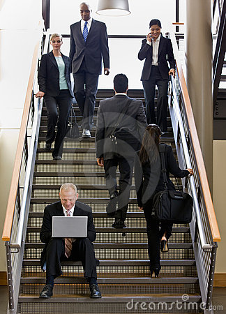 Businessman working on laptop on office stairs