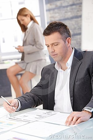 Businessman Working In Office Sitting At Desk Royalty Free Stock Photo - Image: 18068665