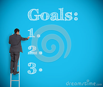 Businessman writing goals on a giant wall