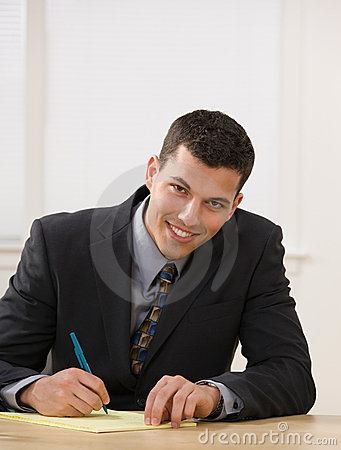Businessman writing on legal pad taking notes