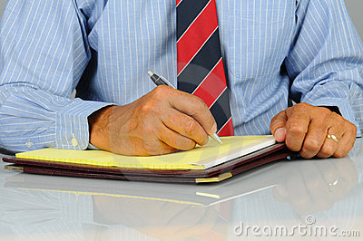 Businessman writing in note pad
