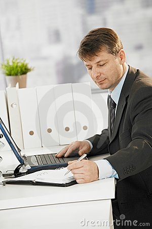 Businessman writing notes to organizer