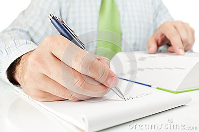 Businessman writing word INFLATION in notepad.