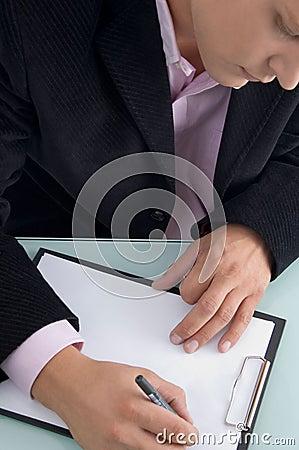 Businessman writing on writing pad