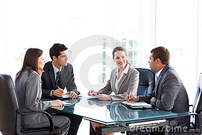 Businessmen and businesswomen talking at a table
