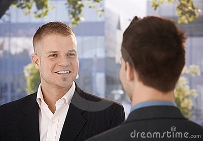 Businessmen chatting outside of office