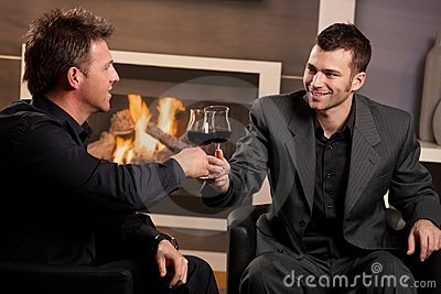 Businessmen clinking wine glasses