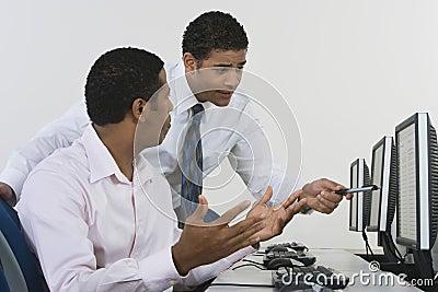 Businessmen Discussing In Computer Lab