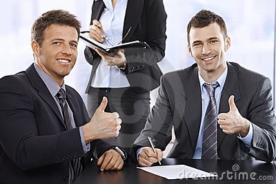 Businessmen giving the thumbs up, smiling