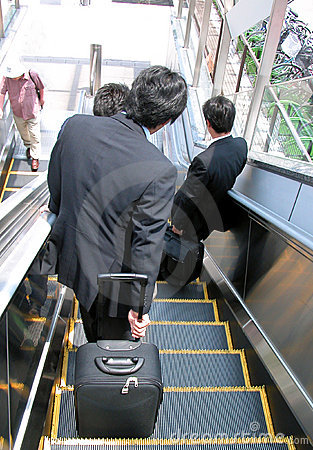 Businessmen on moving staircase