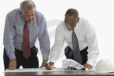 Businessmen reviewing blueprints