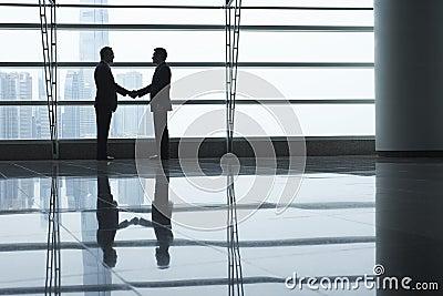 Businessmen Shaking Hands In Airport Terminal