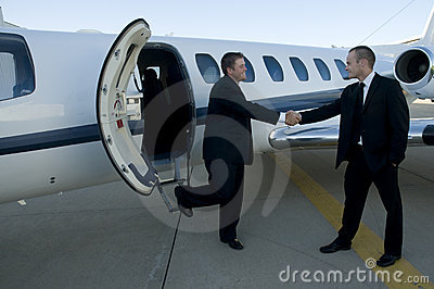 Businessmen shaking hands in front of corporate je
