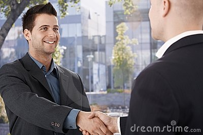 Businessmen shaking hands in front of office
