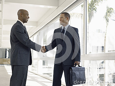 Businessmen Shaking Hands In Office Corridor