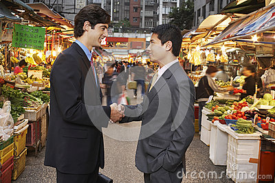Businessmen Shaking Hands At Street Market