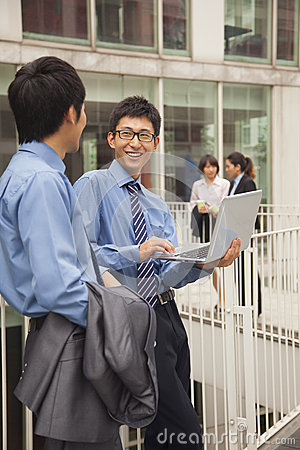 Businessmen smiling and working together outside with laptop