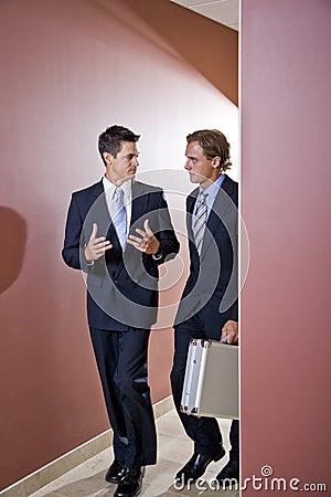 Businessmen talking, walking in office corridor