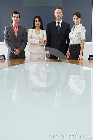 Businessmen and women at conference room table, portrait