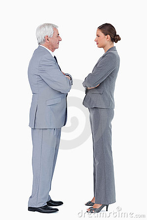 Businesspartner standing face to face with arms folded