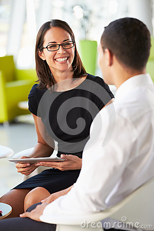 Businesspeople With Digital Tablet Having Meeting InOffice