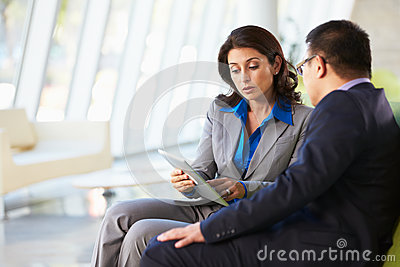 Businesspeople With Digital Tablet Sitting In Modern Office
