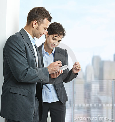 Businesspeople looking at smartphone