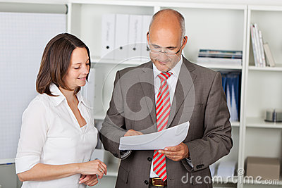 Businesspeople Reading Document In Office