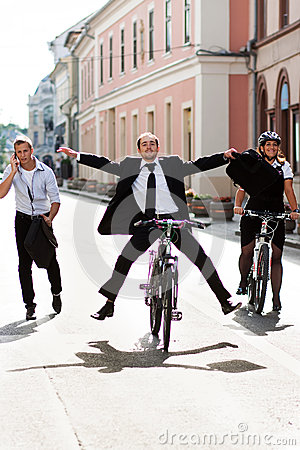 Businesspeople riding on bikes and running