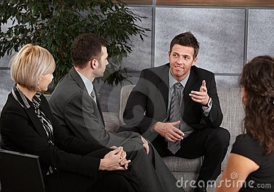 Businesspeople sitting on sofa, talking