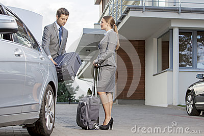 Businesspeople unloading luggage from car outside hotel