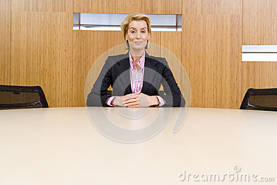 Businesswoman alone at conference table, hands clasped, portrait, low angle view
