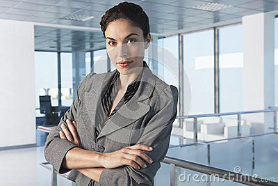 Businesswoman With Arms Crossed In Office Corridor