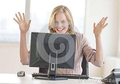 Businesswoman With Arms Raised Celebrating Success While Looking