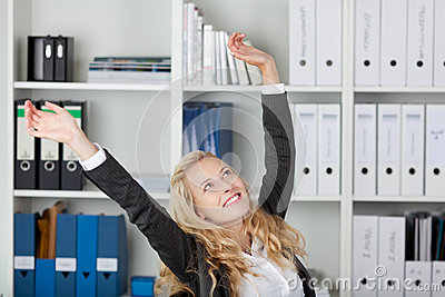 Businesswoman With Arms Raised In Office