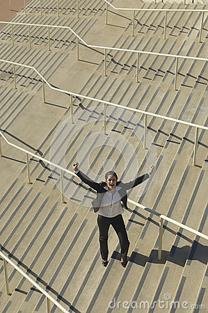 Businesswoman With Arms Raised On Stairs
